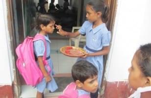 Les filles recoivent le tilak avant d'entrer en classe
