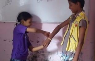 Raksha Bandhan, une fillette attache un bracelet à un camarade
